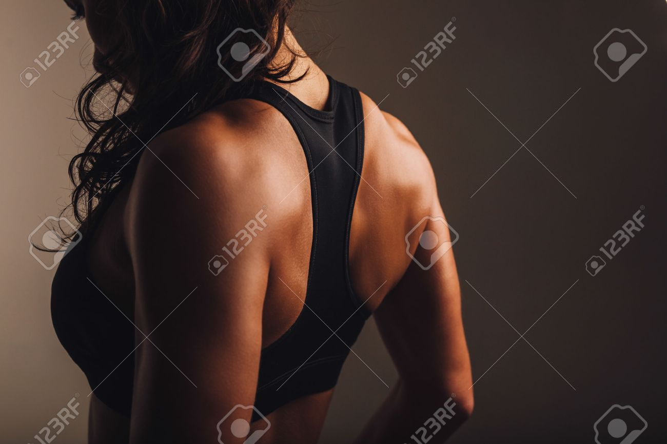 eb8bb6510e Rear view of strong young woman wearing sports bra. Muscular back of a woman  in