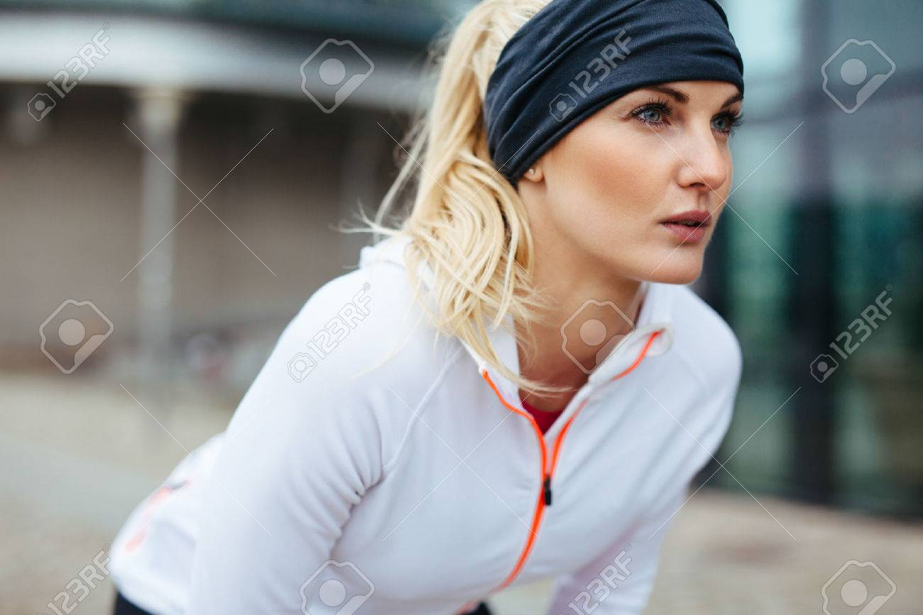 Young woman leaning over in sports gear. Determined sports woman looking forward for run. - 36041557