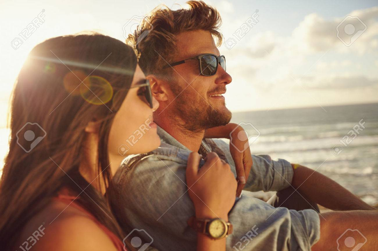 Romantic young couple together outdoors on a summer day. Caucasian couple enjoying the beach view. - 40567880