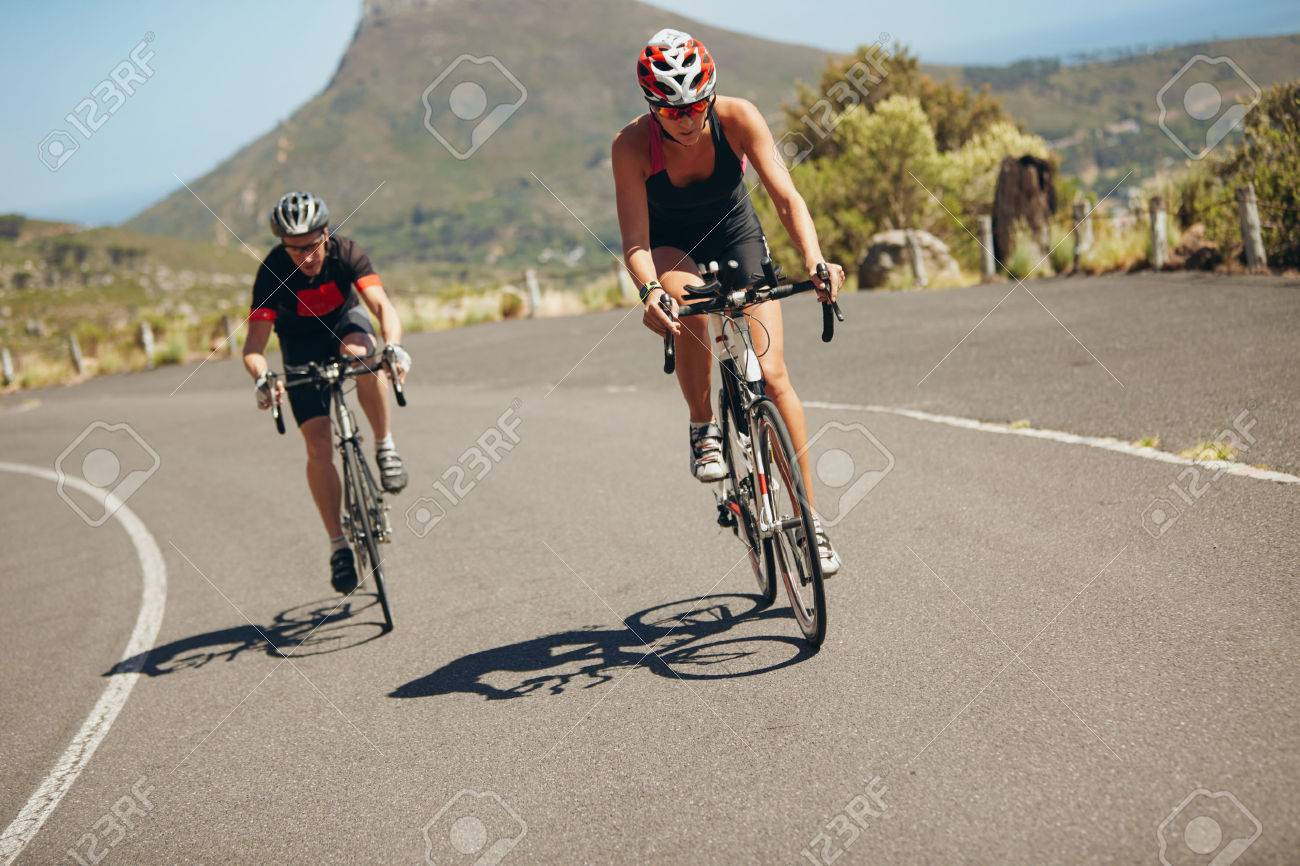 Cyclist riding bikes on open road. Triathletes cycling down the hill on bicycles. Practicing for triathlon race on country road. - 40568055