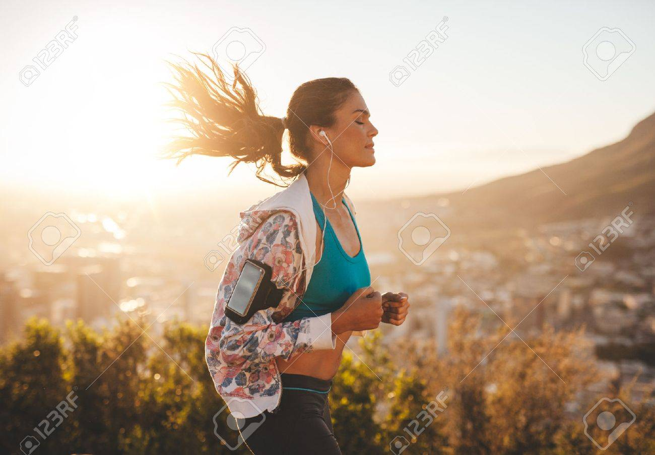 Portrait of beautiful young woman out for a run on a hot sunny day. Caucasian female model jogging outdoors. - 41851548
