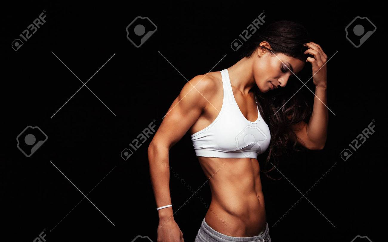 Image of young woman in sports wear thinking while standing against black background. Thoughtful fitness model. Stock Photo - 43375495