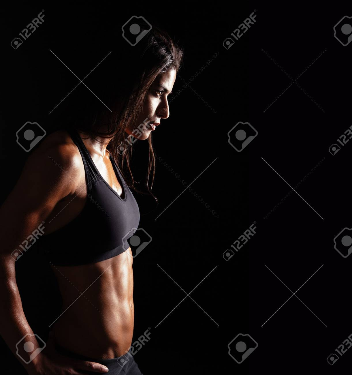 Image of fitness woman in sports clothing looking away on black background. Young female with perfect muscular body. Determination and confidence. - 43375619