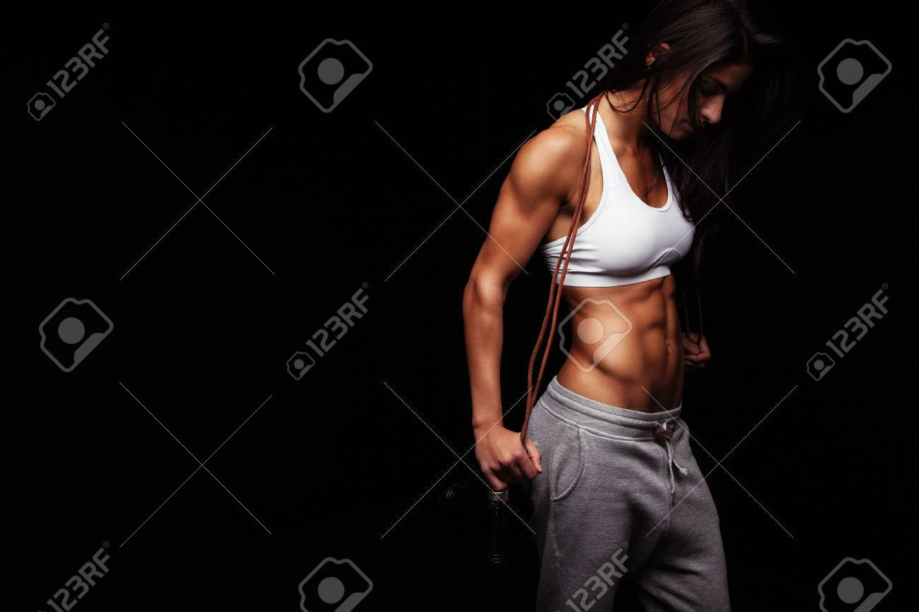 Image of female bodybuilder holding skipping rope looking down. Young fitness woman with muscular body posing on black background Stock Photo - 43647358