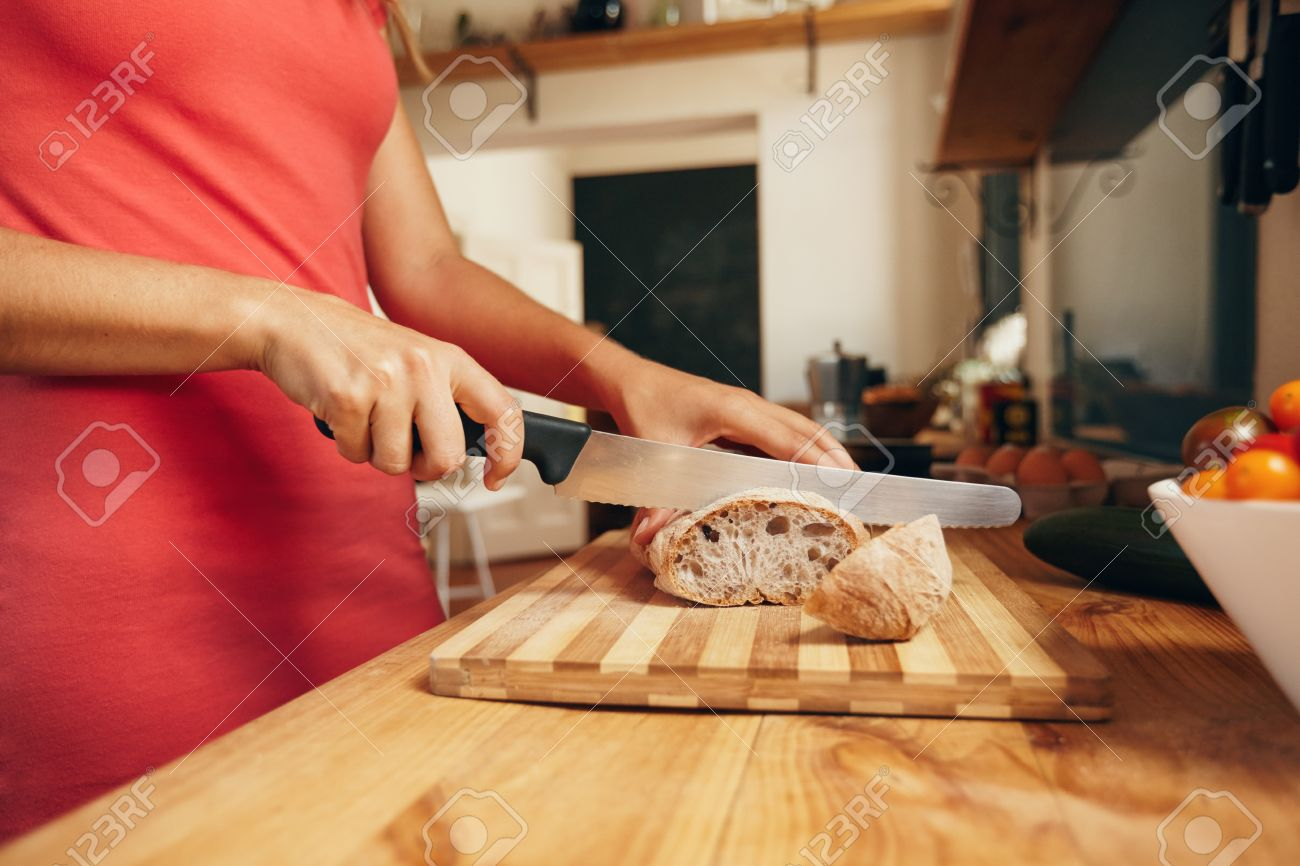 woman slicing loaf of bread on cutting board with kitchen knife stock photo woman slicing loaf of bread on cutting board with kitchen knife close up shot of female hands cutting bread on kitchen counter