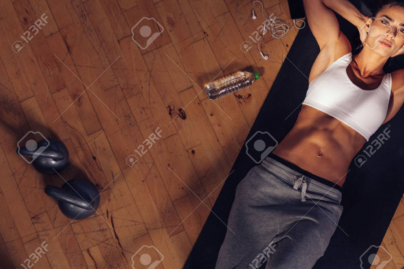 Top view of fitness model lying on exercise mat. Overhead shot of fitness instructor tired resting on mat with water bottle, mobile phone and kettle bell on floor. Stock Photo - 43852848