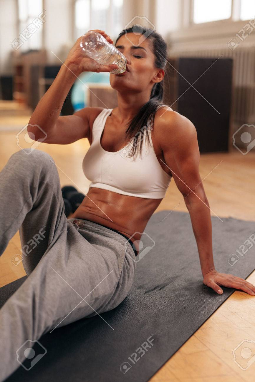 Fit young woman drinking water in the gym muscular woman sitting fit young woman drinking water in the gym muscular woman sitting on exercise mat sciox Choice Image