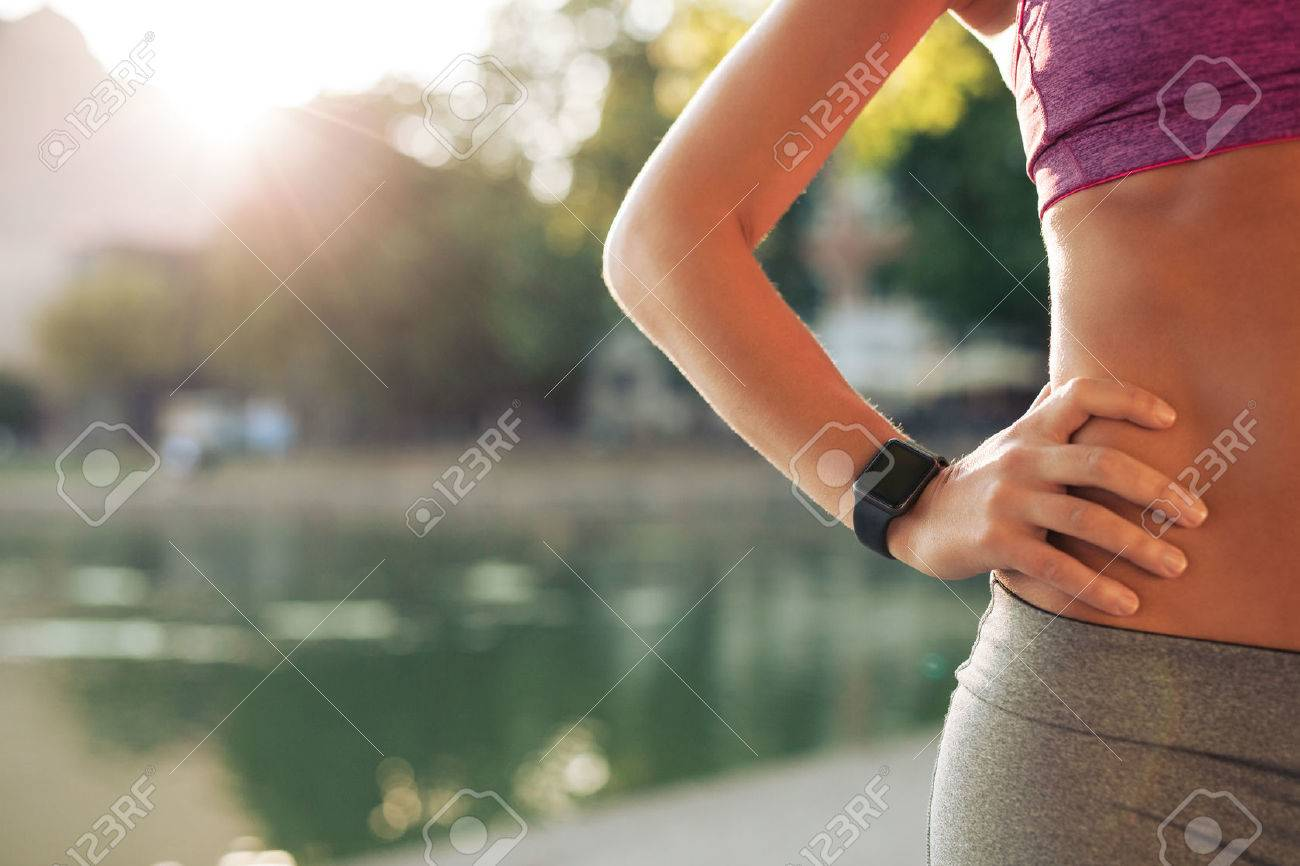Sportswoman wearing smartwatch device. Cropped shot of fit woman in sports wear standing with her hand on hip outdoors, with sun flare. Stock Photo - 44131226