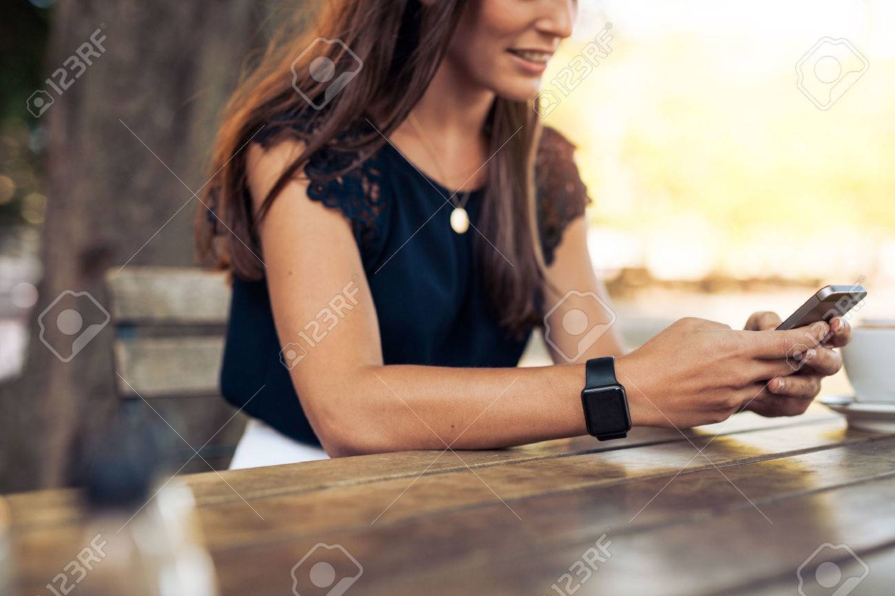 Woman typing text message on smart phone in a cafe. Cropped image of young woman sitting at a table with a coffee using mobile phone. Stock Photo - 44194902
