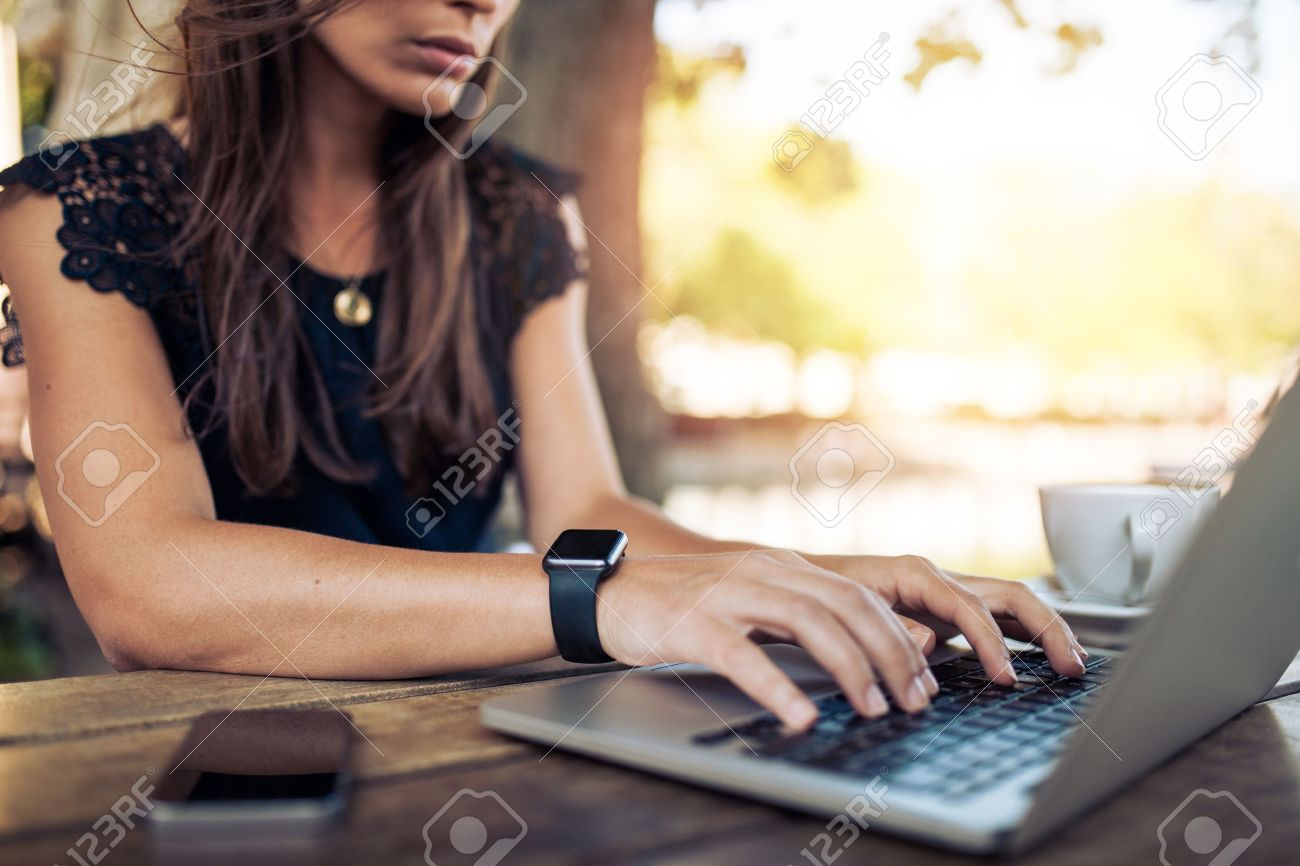 Young woman wearing smartwatch using laptop computer. Female working on laptop in an outdoor cafe. Stock Photo - 44972543