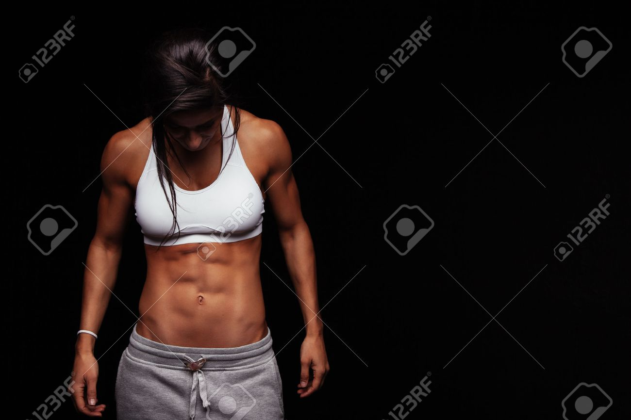 Image of fitness woman in sports clothing looking down. Young female model with muscular body. Horizontal studio shot with copy space on black background. Stock Photo - 45883665