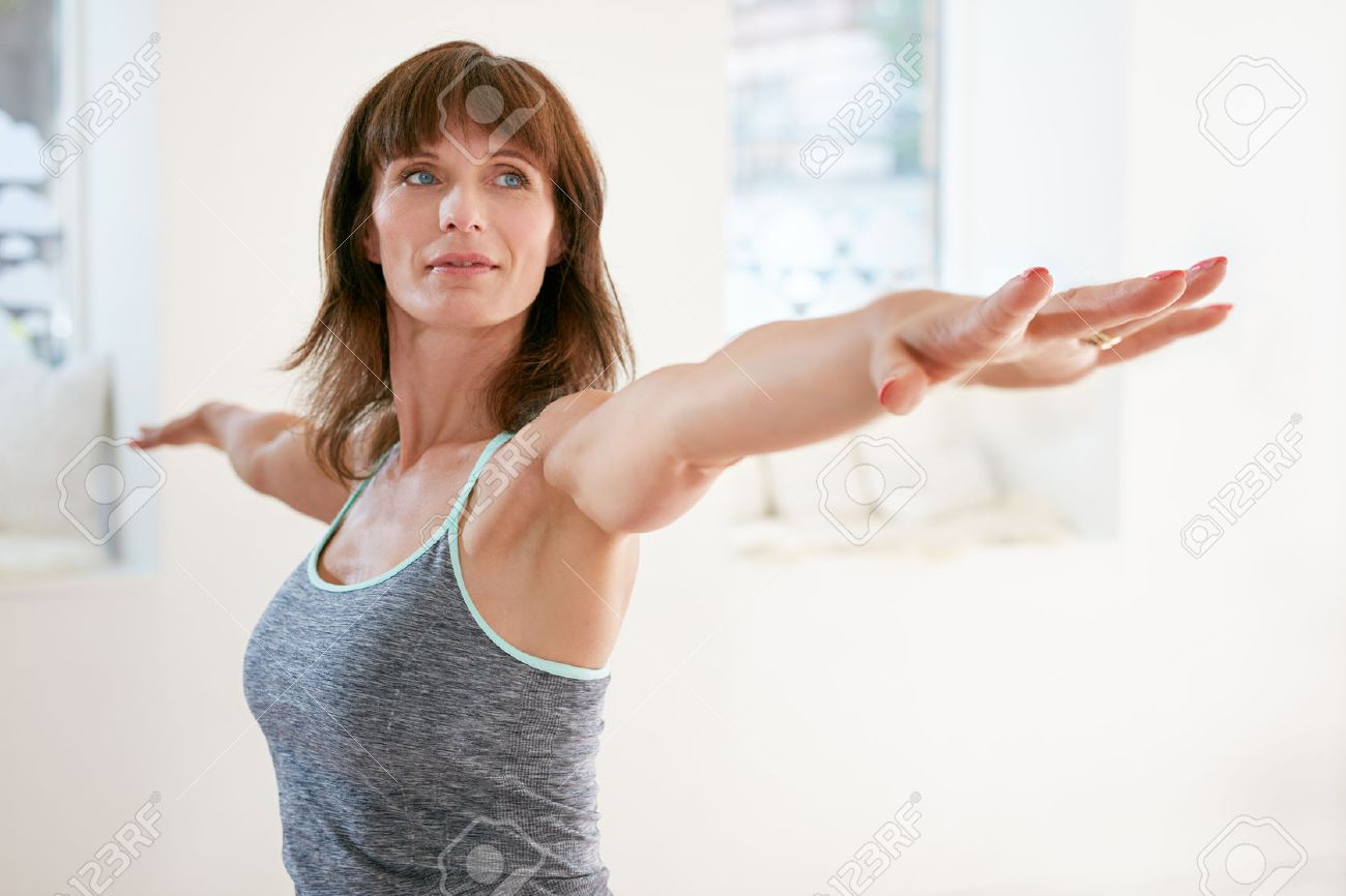 Portrait of mature woman stretching her arms and looking away at gym. Beautiful woman performing yoga in warrior pose, Virabhadrasana. - 46646515