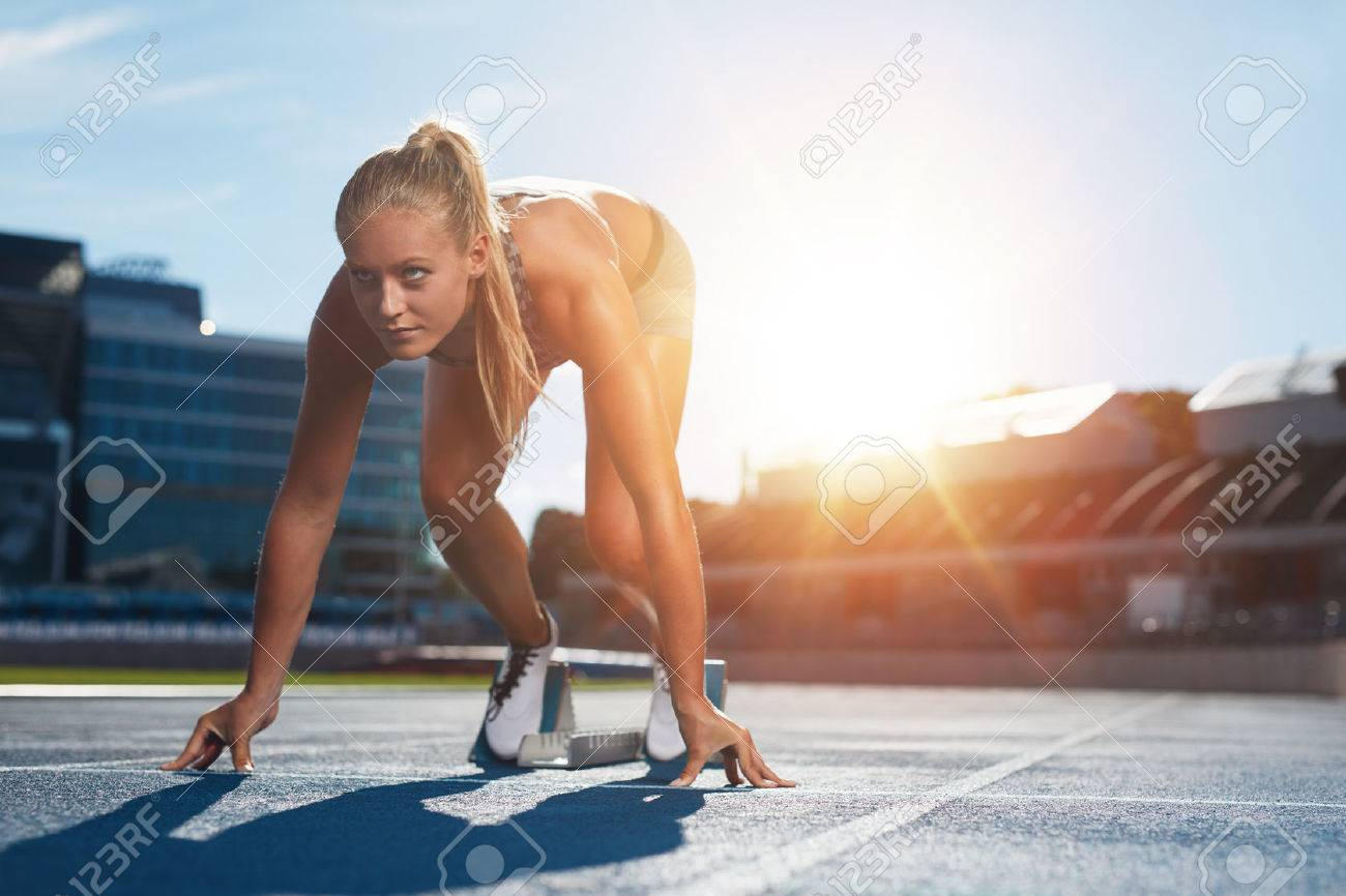 Professional female track athlete in set position on sprinting blocks of an athletics running track. Runner is in a athletics stadium with bright sunlight. - 46875016