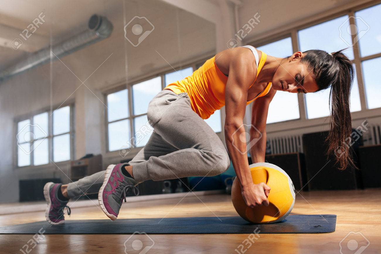 Fit female doing intense core workout in gym. Young muscular woman doing core exercise on fitness mat in health club. - 46946667