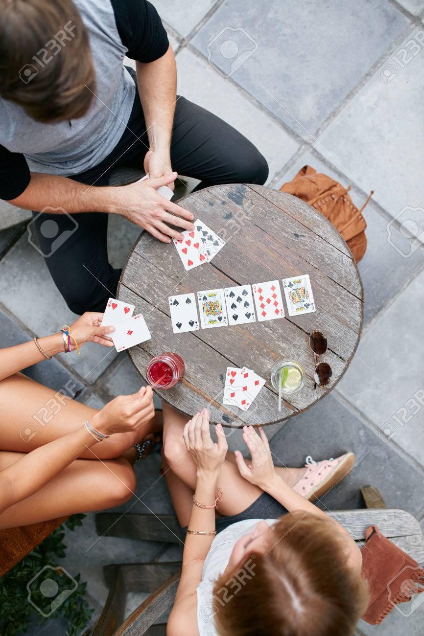 Immagini Stock Tre Giovani Amici Che Giocano A Carte Al Caffe Direttamente Sopra Il Colpo Di Giovane Uomo E Donna Seduti Attorno A Un Tavolino Di Un Caffe All Aperto E Giocare