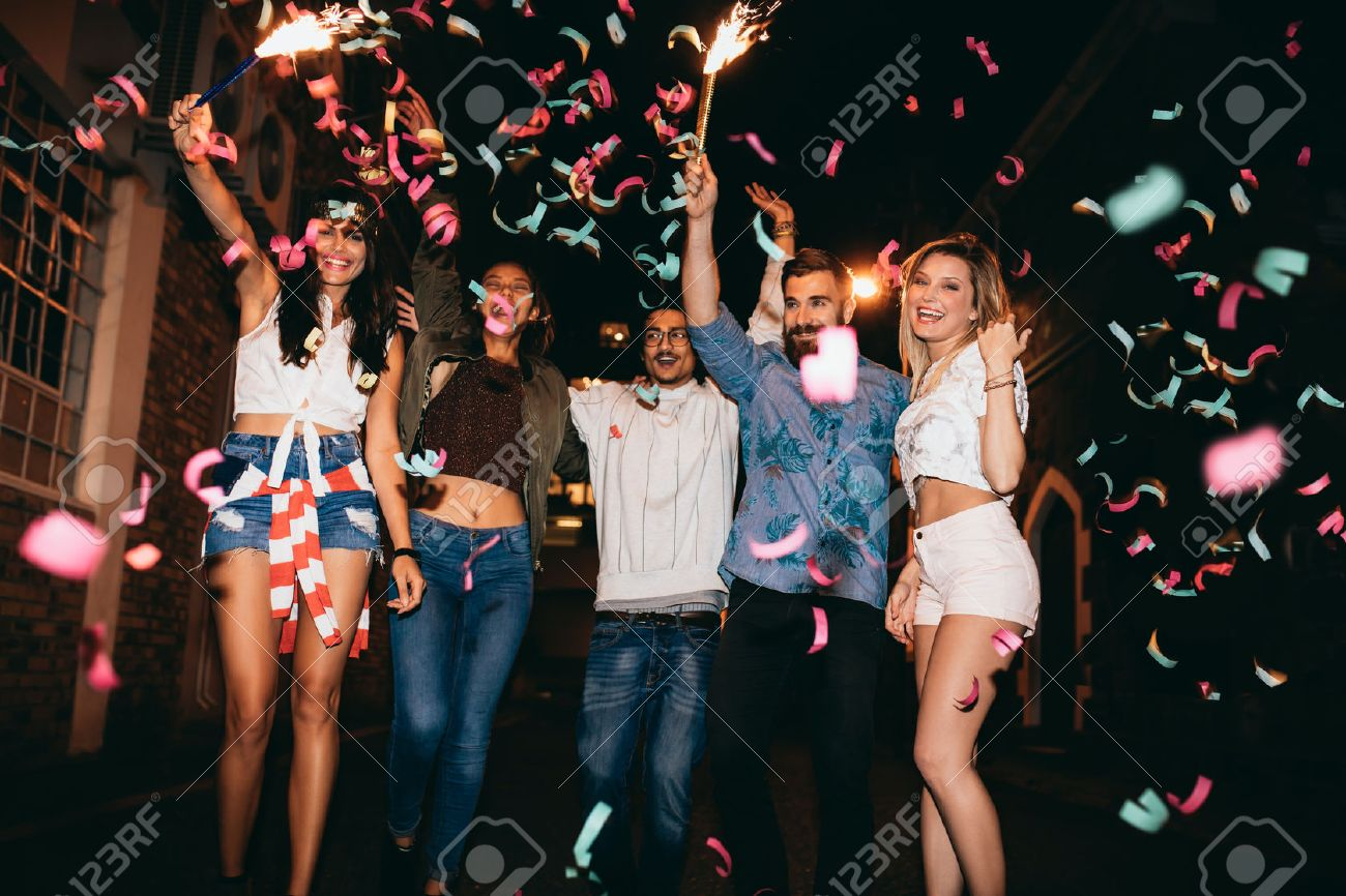 Group of young people having a party, outdoors. Multiracial young men and women celebrating with confetti. Best friend having party at night. Stock Photo - 48840549