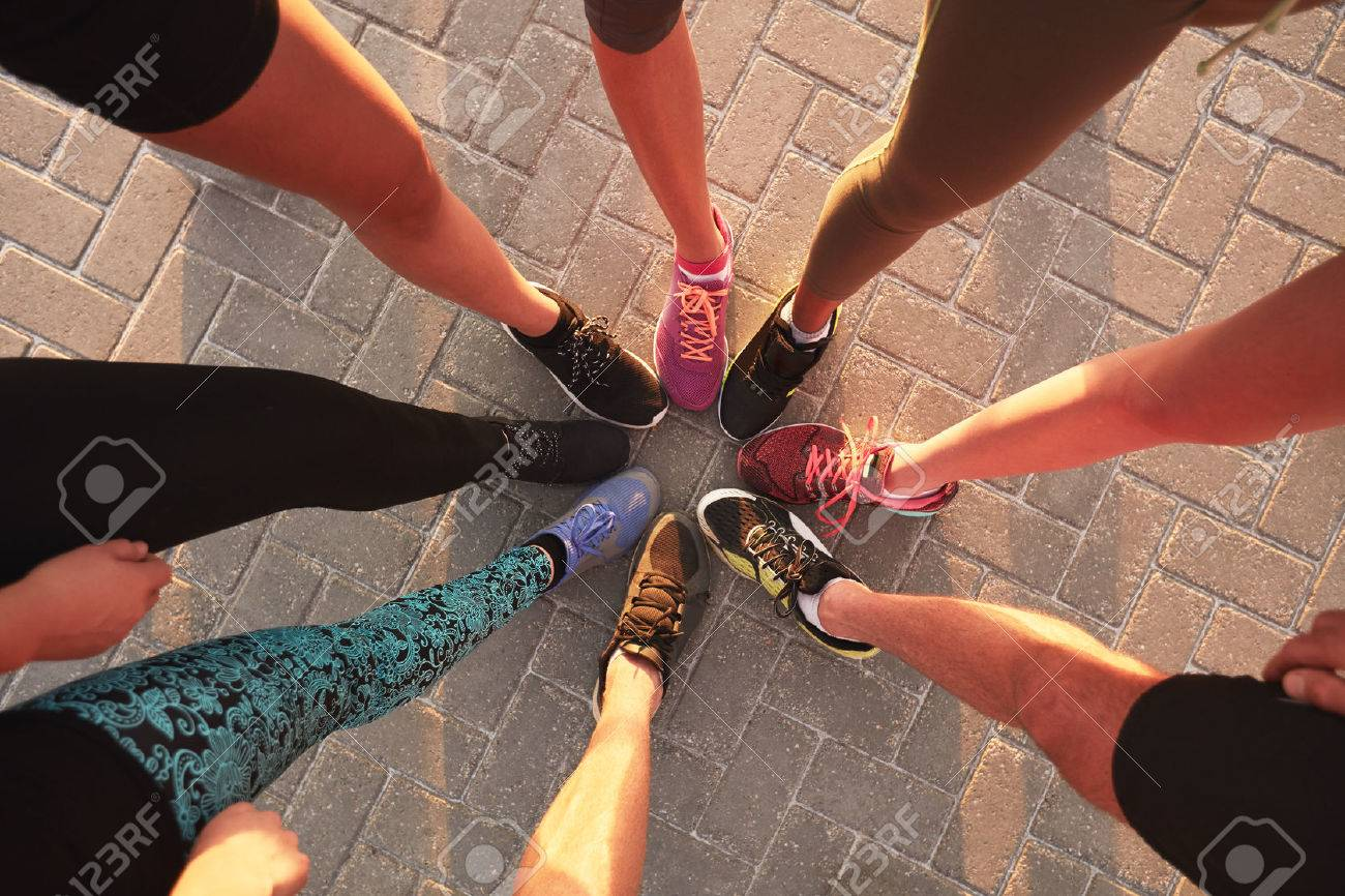 Legs of athletes wearing sports shoes in a circle. Top view of runners standing together. - 50750258