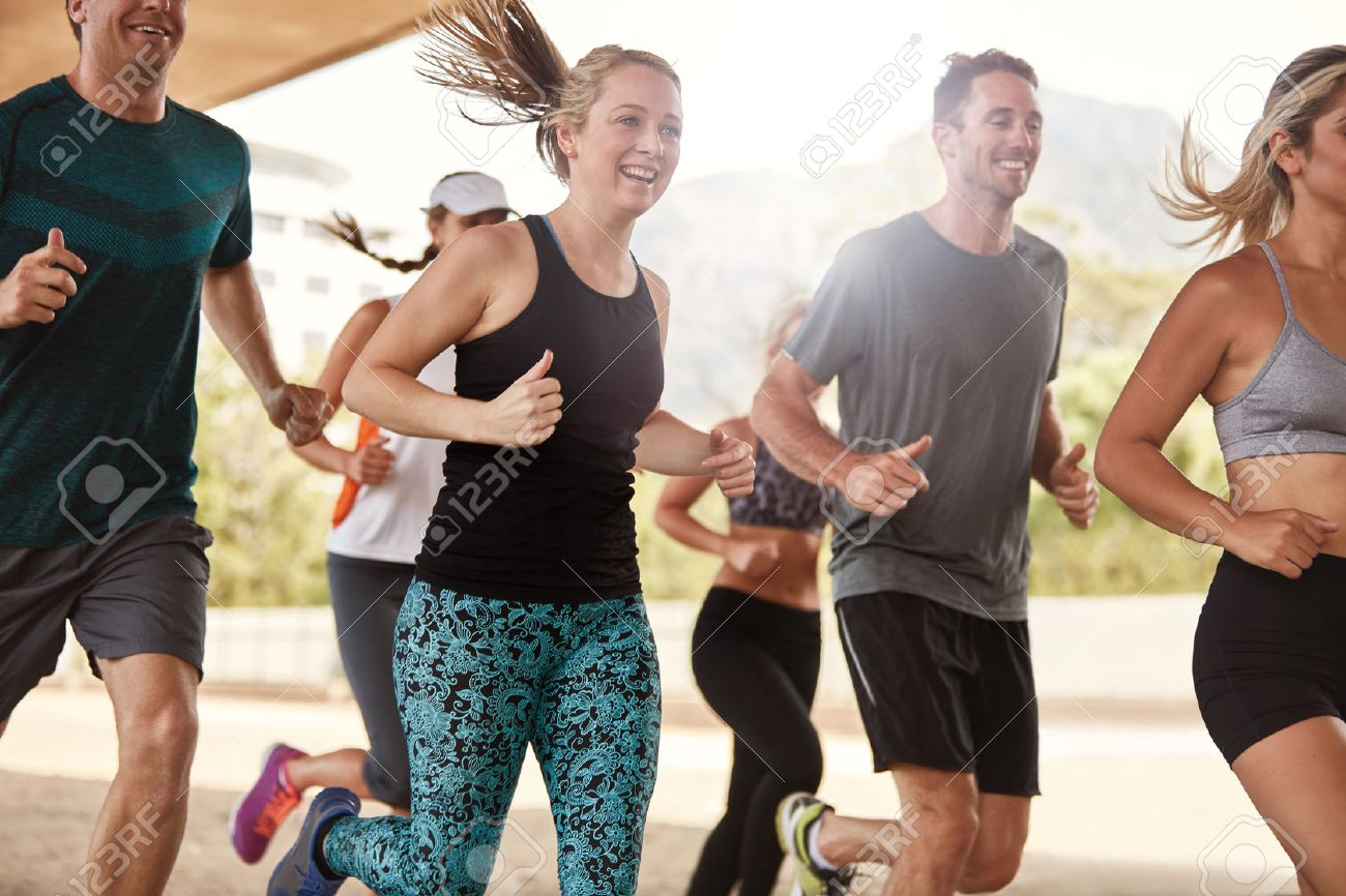 Group of happy young friends running together. Running club members exercising. - 50750353