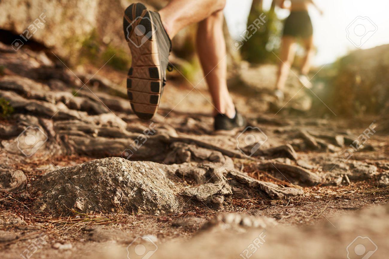 Cross country running. Closeup of male feet run through rocky terrain. Focus on shoes. - 50750434