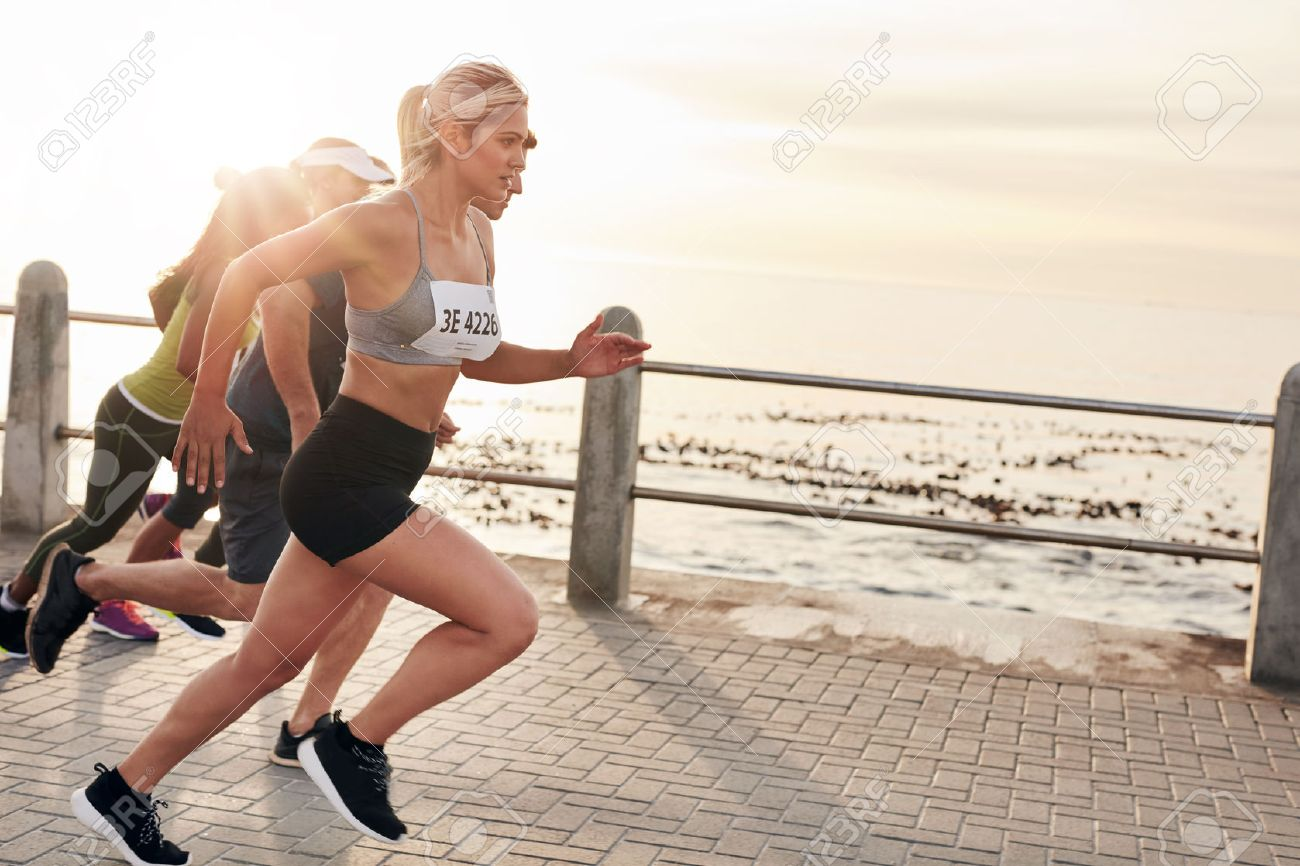 Portrait of young people running on seaside promenade. Group of women running marathon. - 50840004