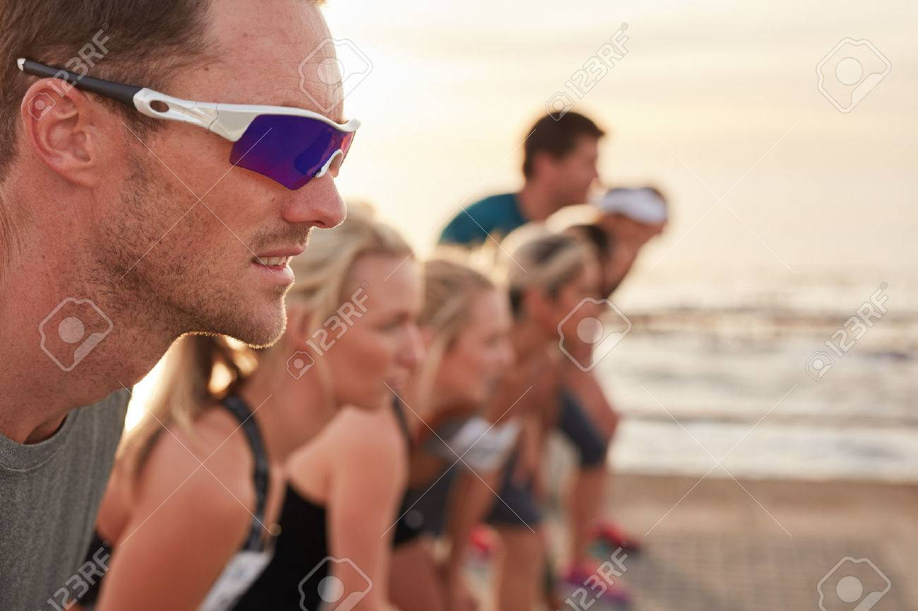 Closeup shot of focused and determined young man standing at starting line with competitors in background. Runners standing at starting line of a marathon race. - 50988681