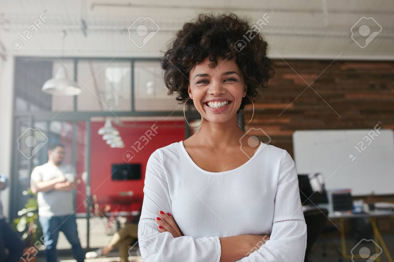 Smiling young woman standing with her arms crossed and looking at camera. She is standing in a modern office with her colleagues in the background. - 51078481
