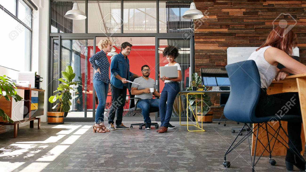 Portrait of group of creative people having a meeting with a laptop in a modern office. Business people having relaxed conversation over new project. - 51510750