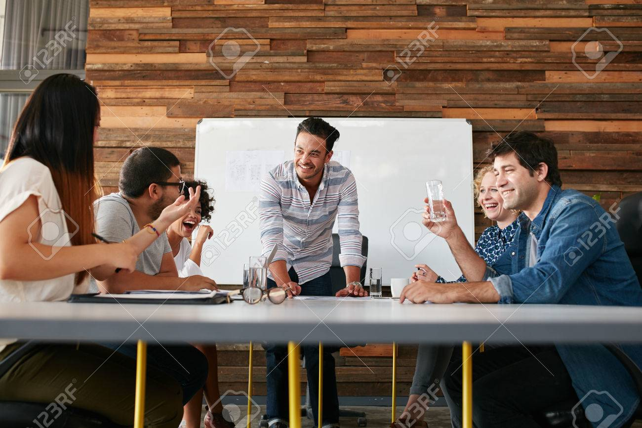 Group of happy young people having a business meeting. Creative people sitting at table in boardroom with man explaining business strategy. - 51510795