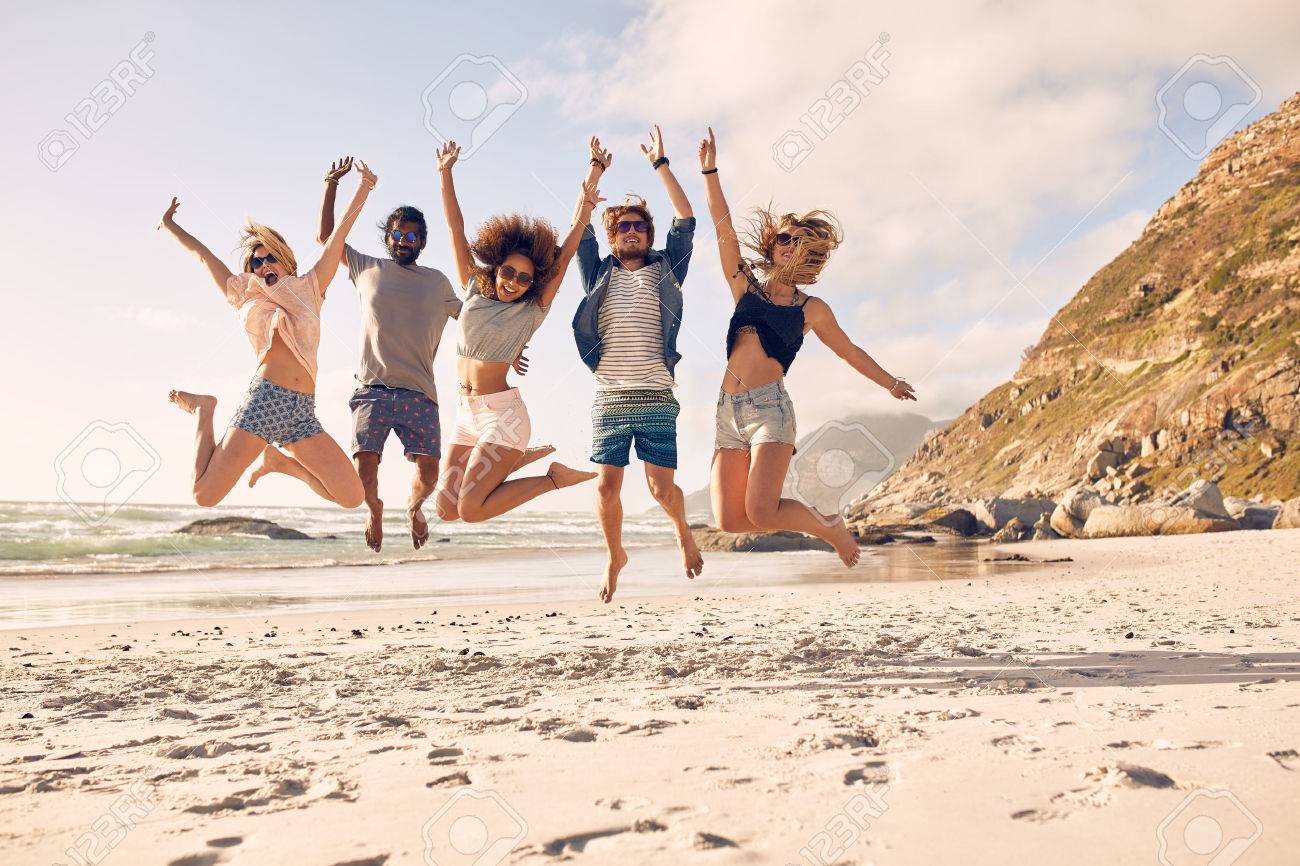 Group of friends together on the beach having fun. Happy young people jumping on the beach. Group of friends enjoying summer vacation on a beach. - 51685898