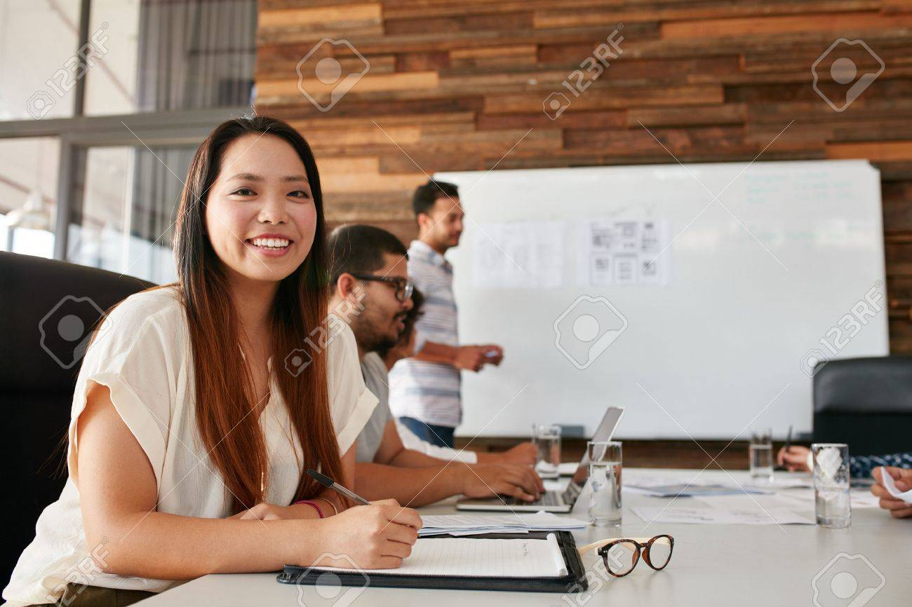 Portrait of happy young woman sitting at conference table with colleagues in background. Asian woman looking at camera smiling while sitting in a business presentation. - 51770041