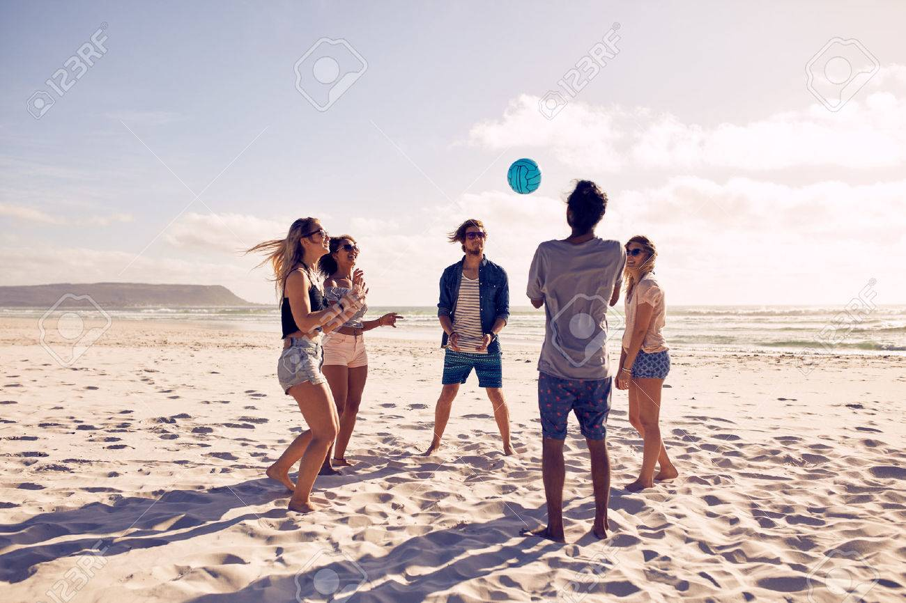 Group of young people playing with ball at the beach. Young friends enjoying summer holidays on a sandy beach. - 51998828