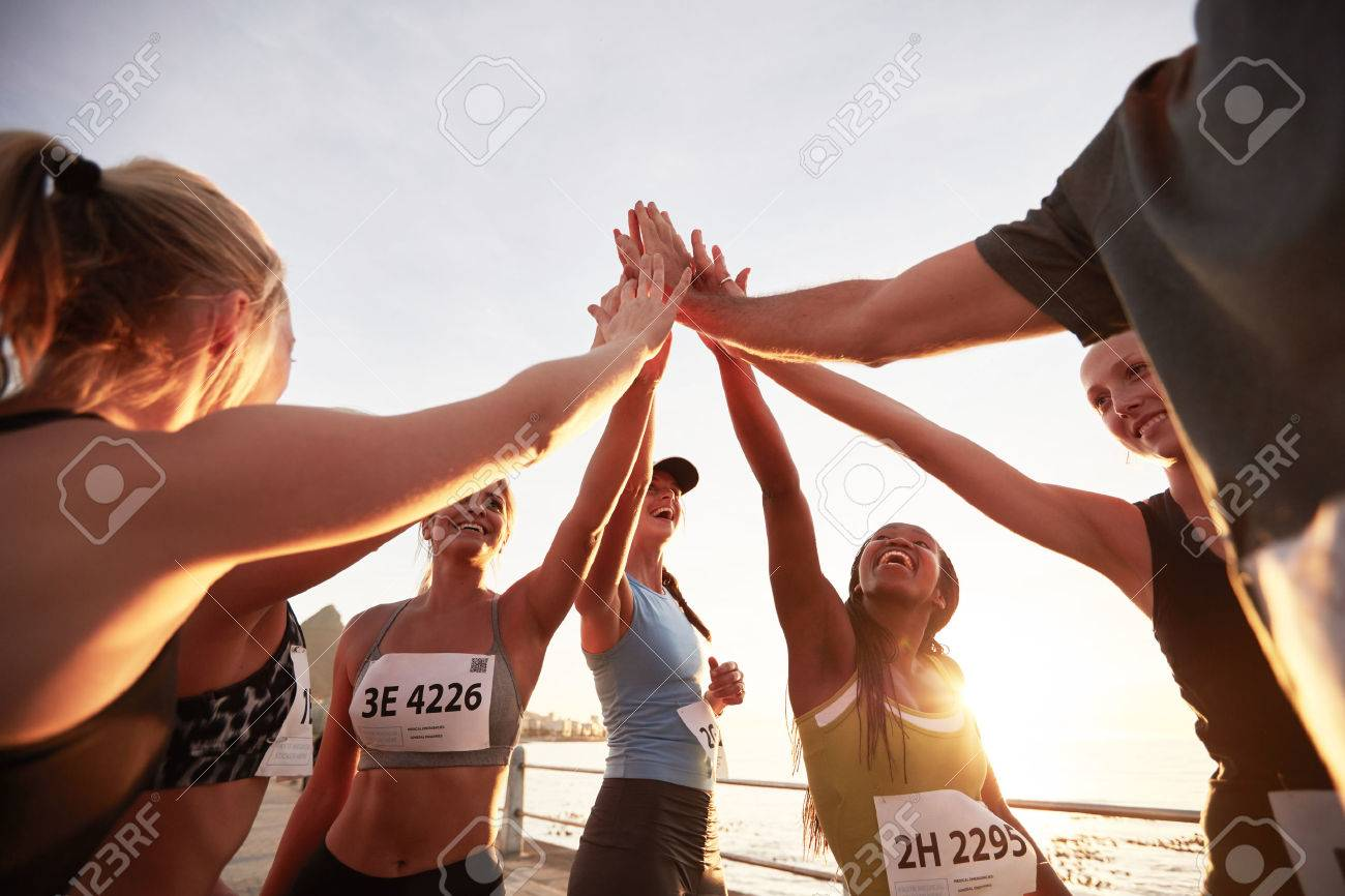 Runners high fiving each other after a good training session. Group of athletes give each other high five after race. - 52020948