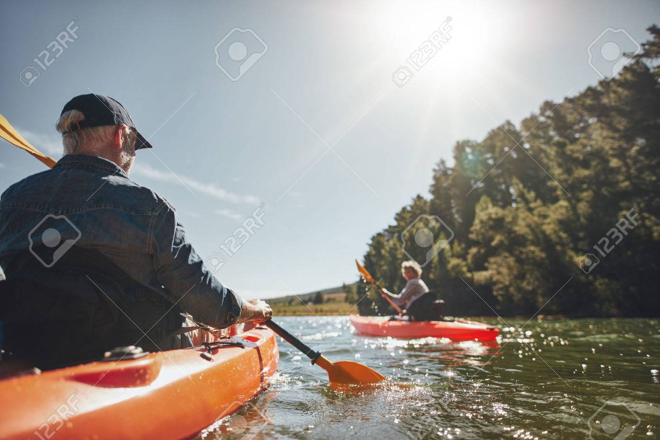 Image of senior couple canoeing in the lake on a sunny day. Kayakers in the lake paddling. - 52328687