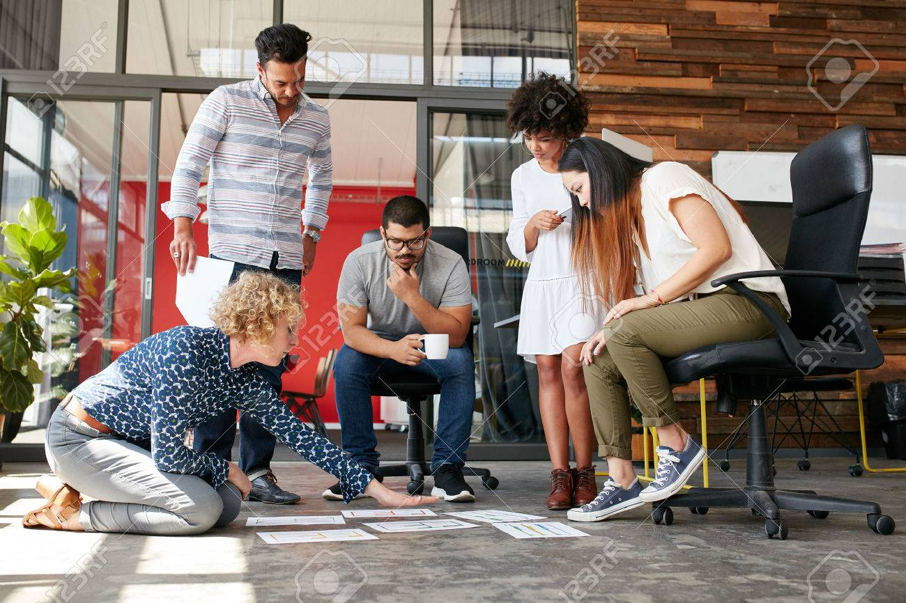 Creative people looking at project plan laid out on floor. Mixed race business associates discussing new project plan in modern office. - 52328689