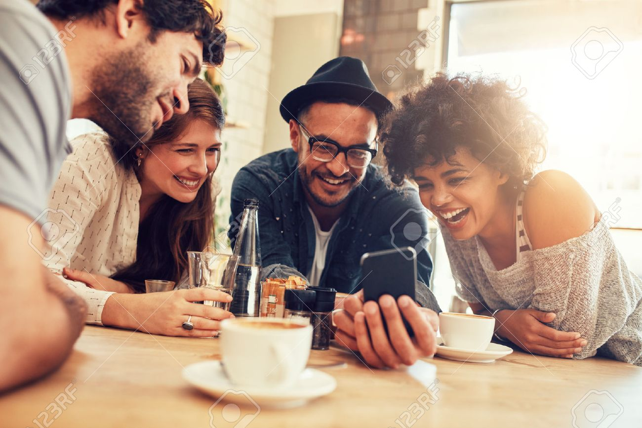 Portrait of cheerful young friends looking at smart phone while sitting in cafe. Mixed race people sitting at a table in restaurant using mobile phone. - 52407809