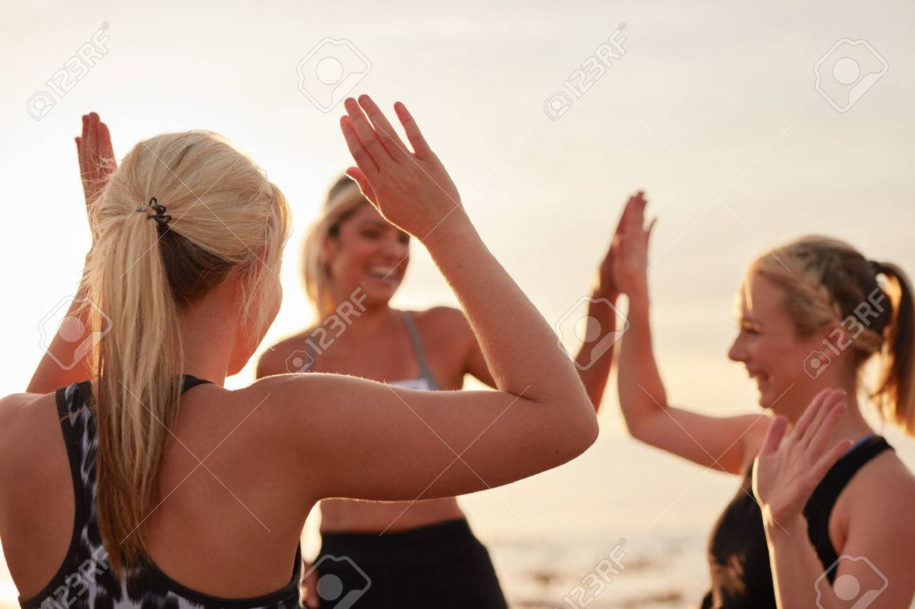 Runners giving high five to each other after a good training session. Group of athletes celebrating success. Stock Photo - 52549190
