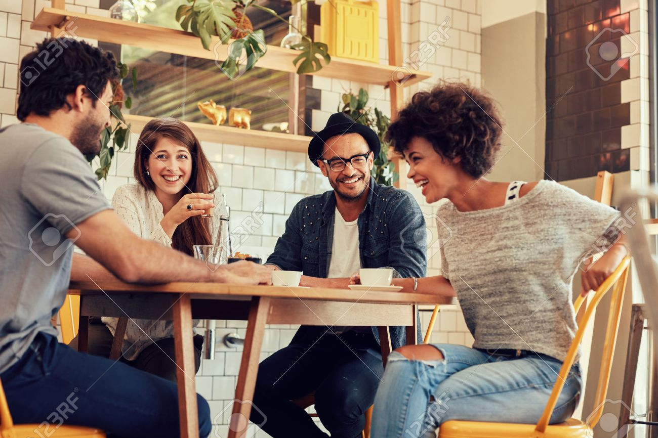 portrait of cheerful young friends having fun while talking in