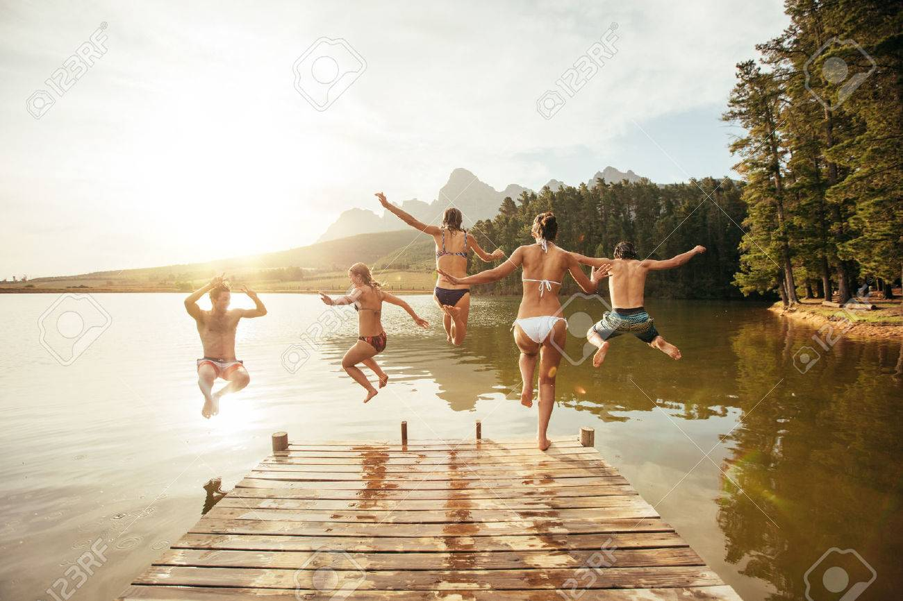 Portrait of young friends jumping into the water from a jetty. Young people having fun at the lake on a summer day. - 52898618