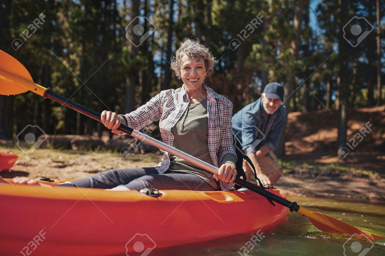 Portrait of happy senior woman in a kayak holding paddles. Woman canoeing with man in background at the lake. - 53055638