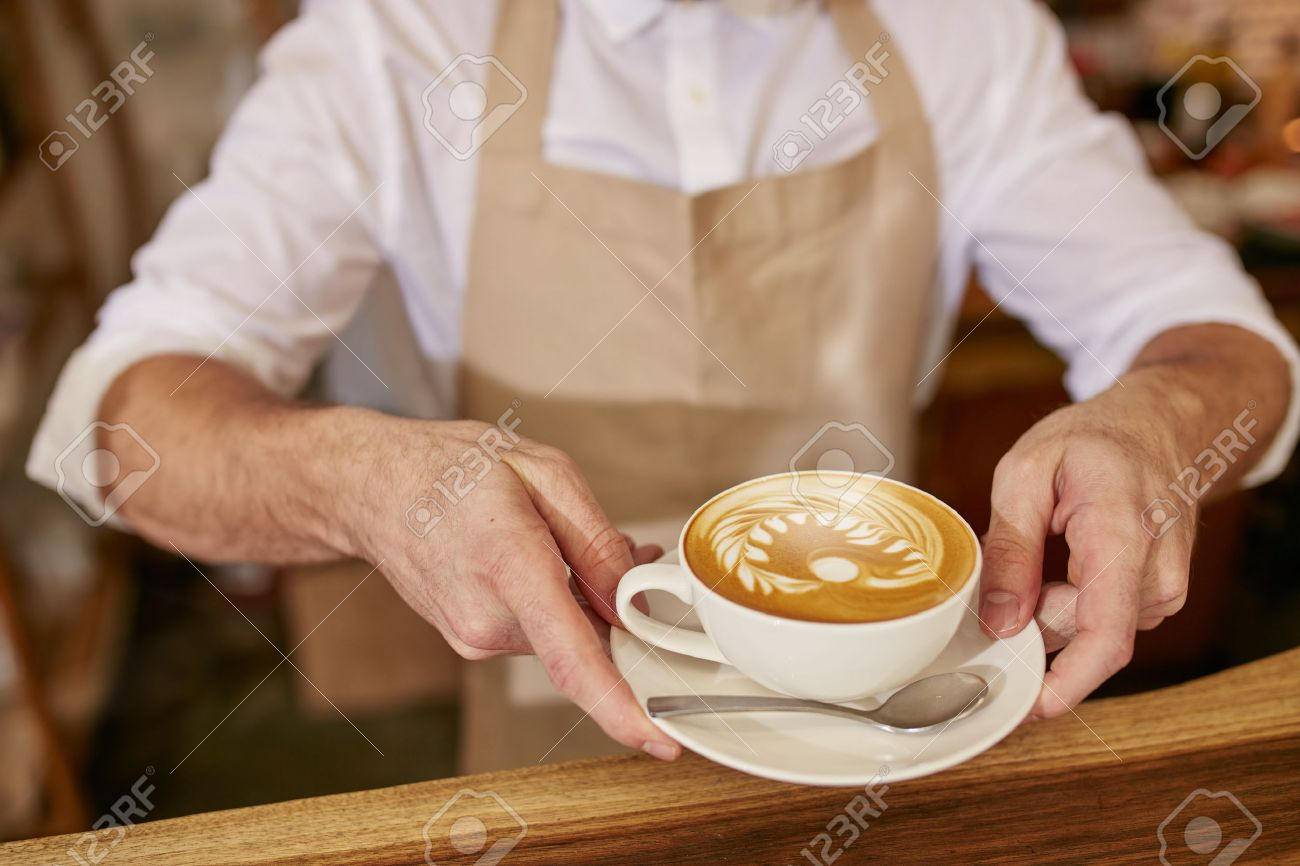 closeup of man in apron serving coffee while standing in coffee  - closeup of man in apron serving coffee while standing in coffee shopbarista