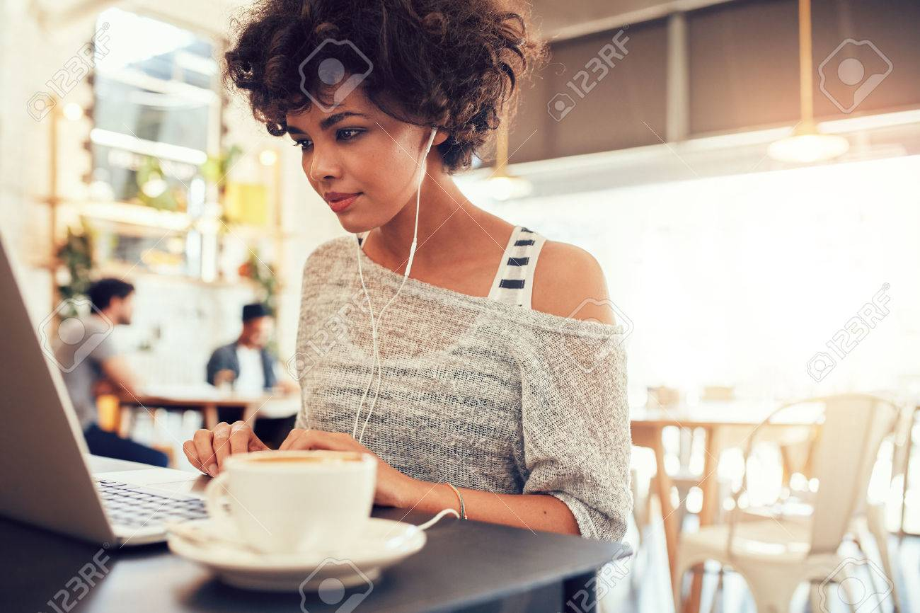 Portrait of an attractive young woman with earphones using laptop at a cafe. African american woman working on laptop computer at a coffee shop. - 53227907
