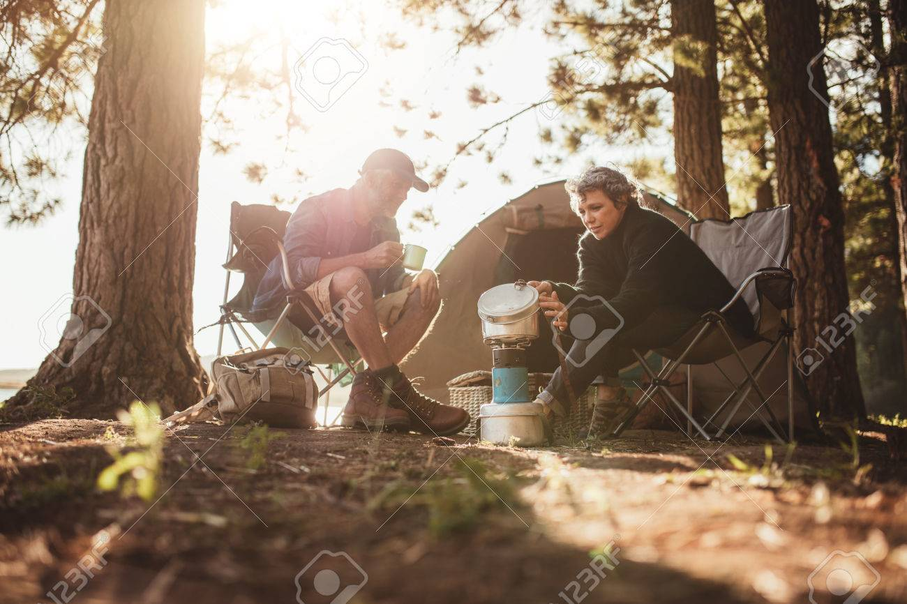 Senior couple cooking and making food outdoors on a camping trip. Mature man and woman sitting outside the tent on a summer day at campsite. - 53227909