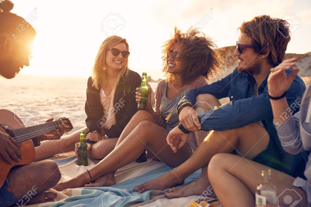 Portrait of group of young friends having a party on the beach in evening. Men and women drinking beers and listening to friend playing guitar. Stock Photo - 53534218