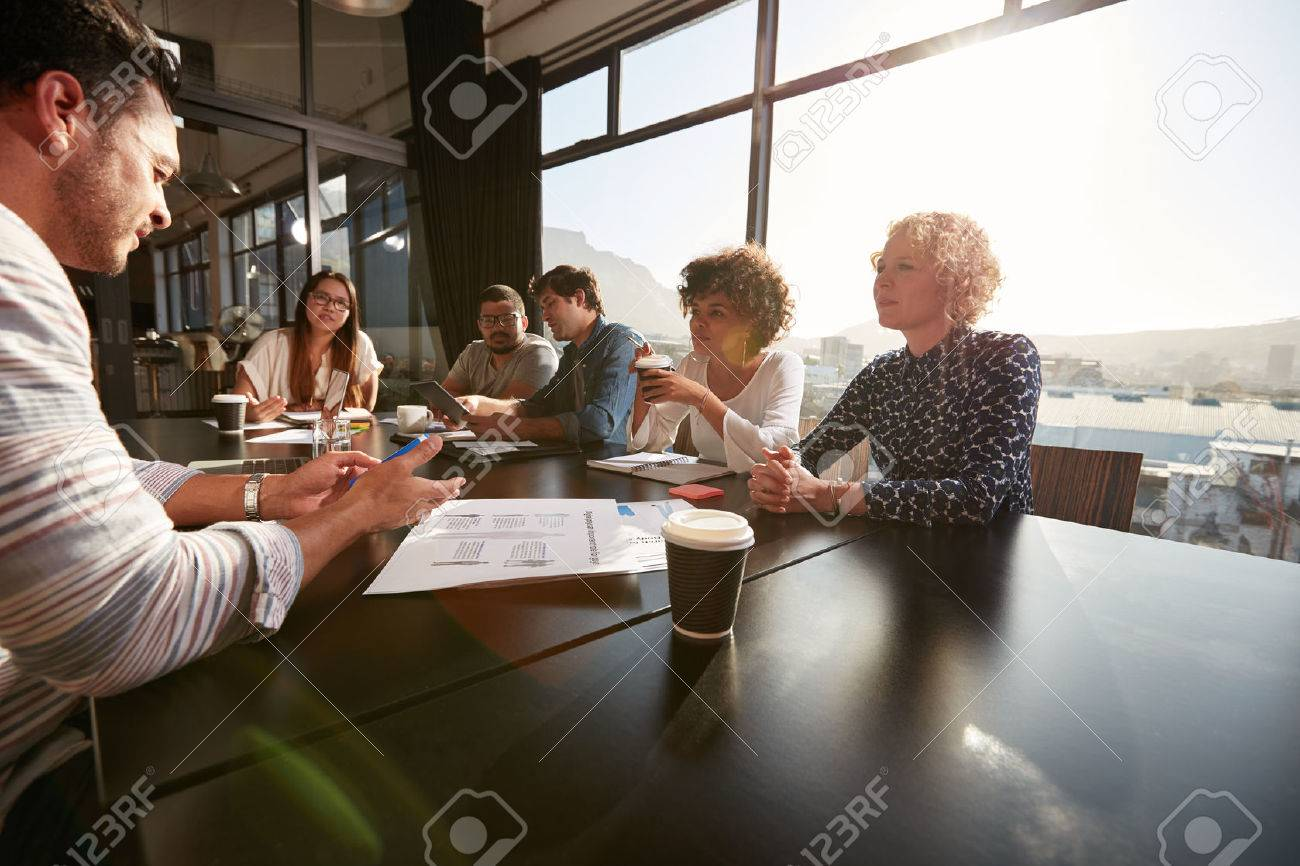 Portrait of creative team sitting around a table discussing new project plans. Mixed race people meeting in office. - 54066148