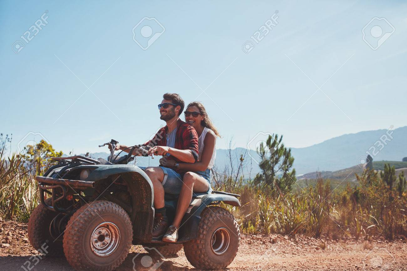 young man and woman riding on a quad bike couple on holiday stock