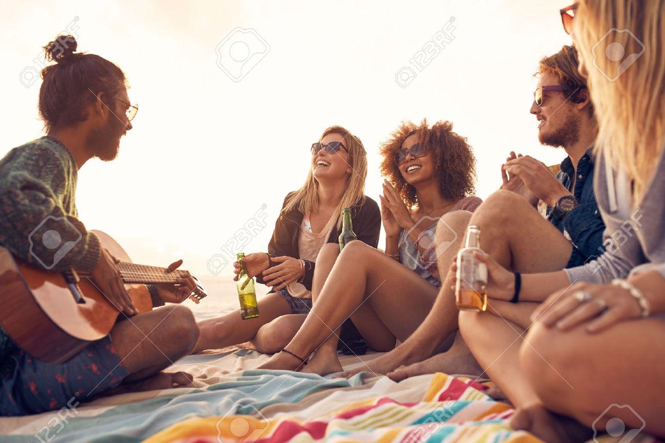 Happy hipsters relaxing and playing guitar at the beach. Friends drinking beers and listening to music. Having fun at beach party in evening. Banque d'images - 54740375