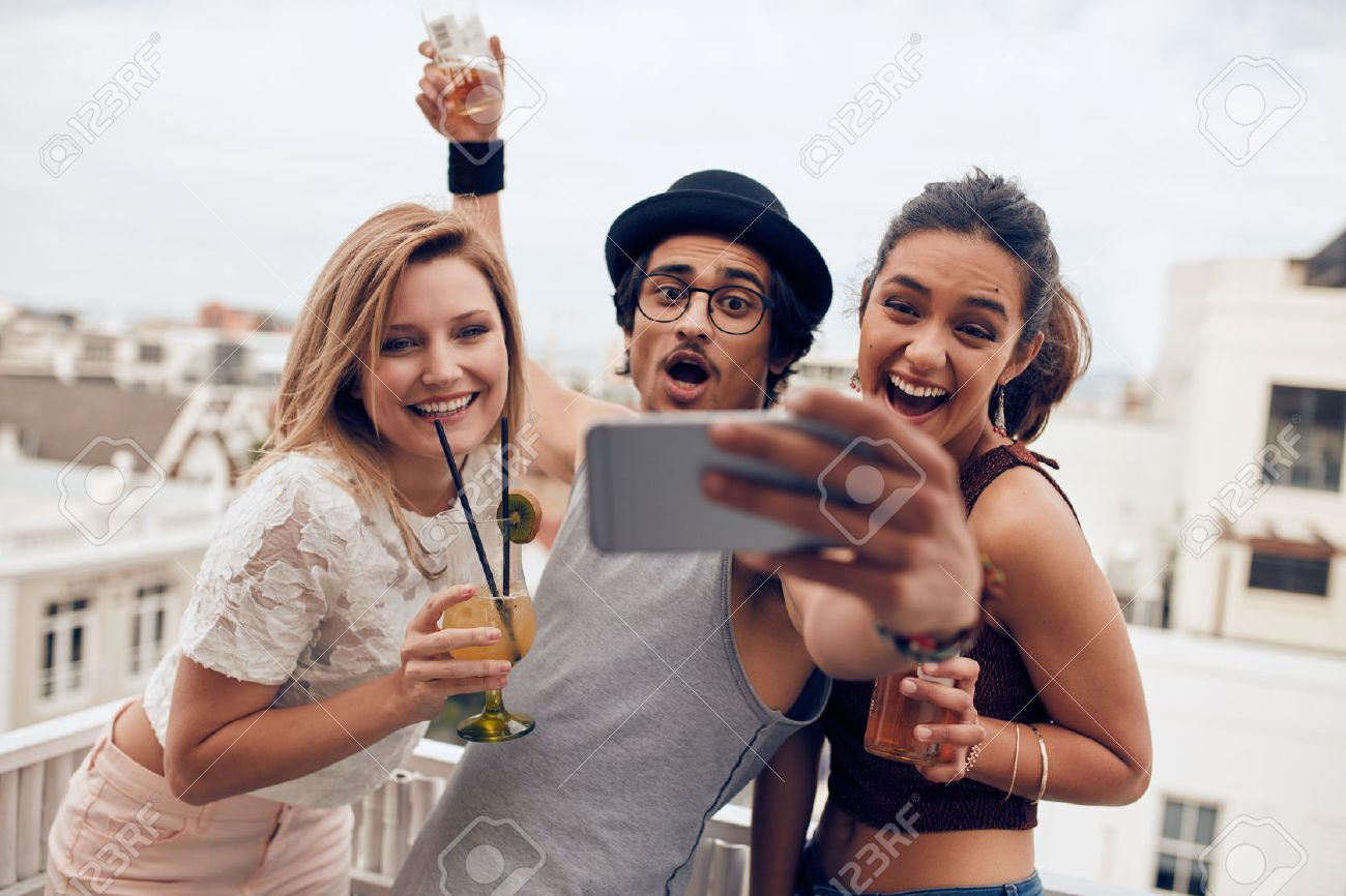 Excited young people taking self portrait with mobile phone during a party. Happy young man and woman taking self portrait at rooftop party. Multiracial people having fun in party with drinks. - 55352771