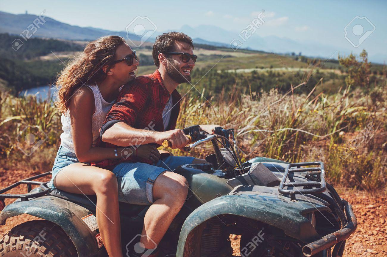 L'homme et la femme se amuser sur une aventure hors route. Couple à cheval sur un vélo de quad dans la campagne sur une journée d'été. Banque d'images - 55353004