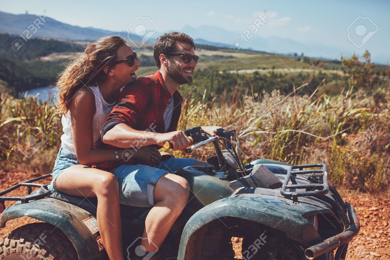 Man and woman having fun on an off road adventure. Couple riding on a quad bike in countryside on a summer day. Foto de archivo - 55353004