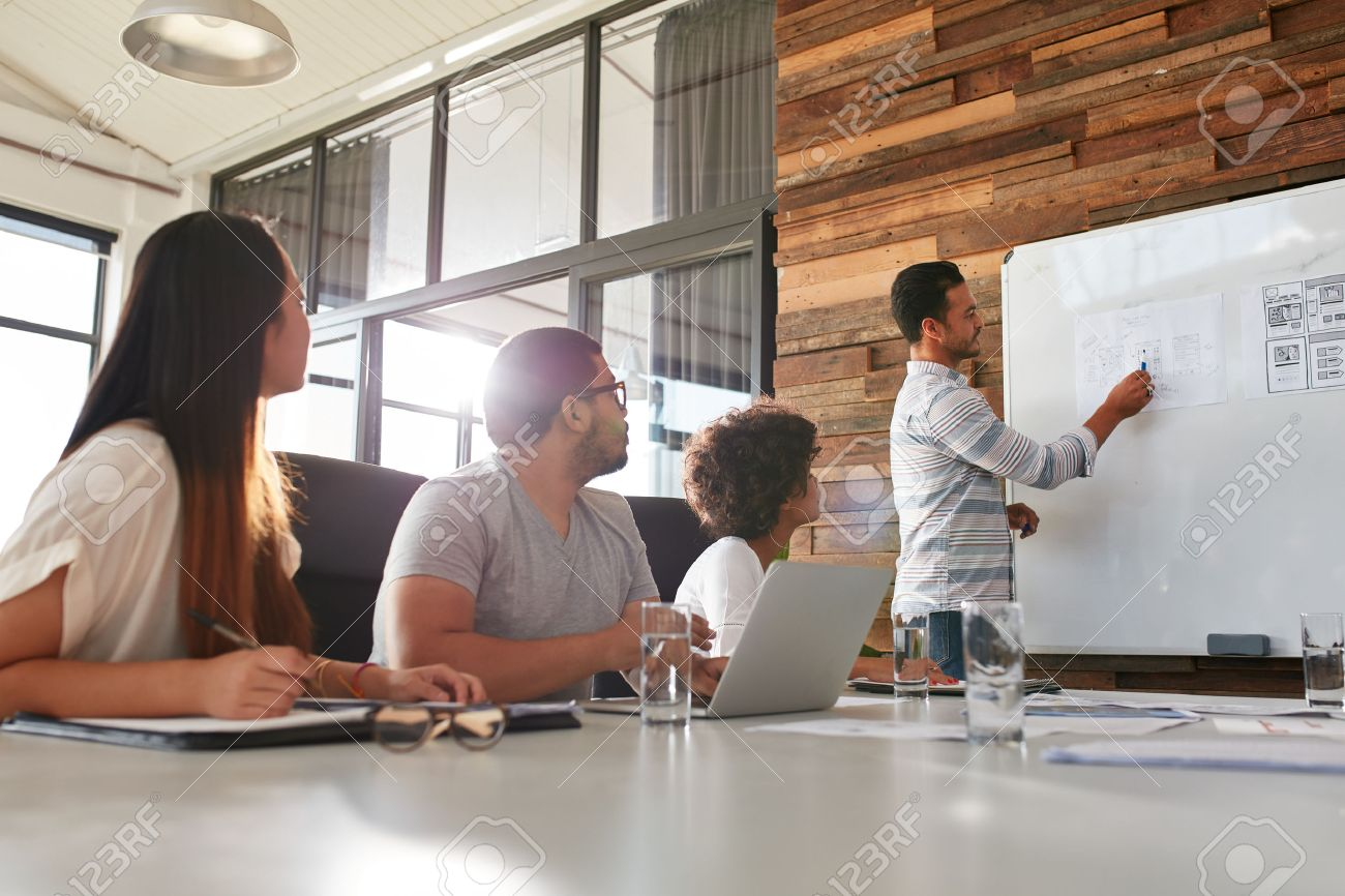 Shot of a male office worker giving creative presentation to his colleagues. Businessman explaining business plan to coworkers in conference room. - 56096901